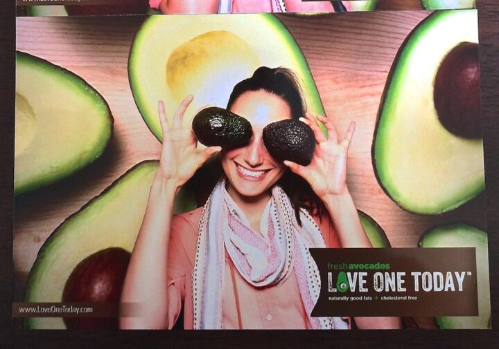 Girl holding two avocados over her eyes and smiling with pictures of avocados behind her.