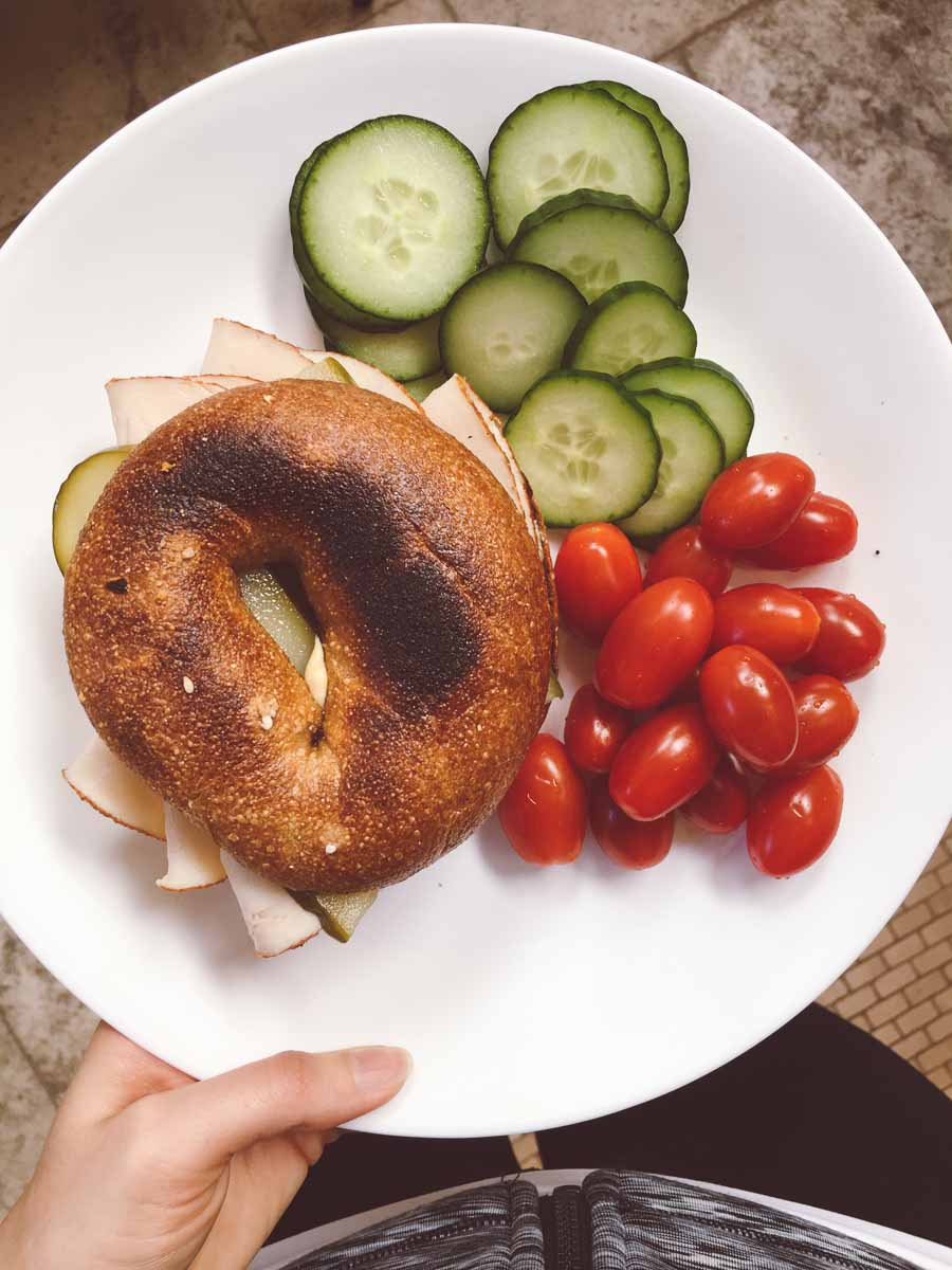 What a dietitian eats in a week - turkey bagel sandwich with cherry tomatoes and sliced cucumber