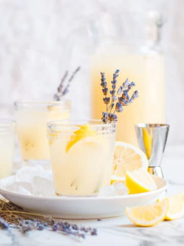 lavender lemonade cocktail with white background a pitcher of lemonade