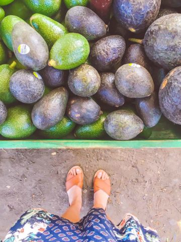 Feet standing at a avocado stand in Maui