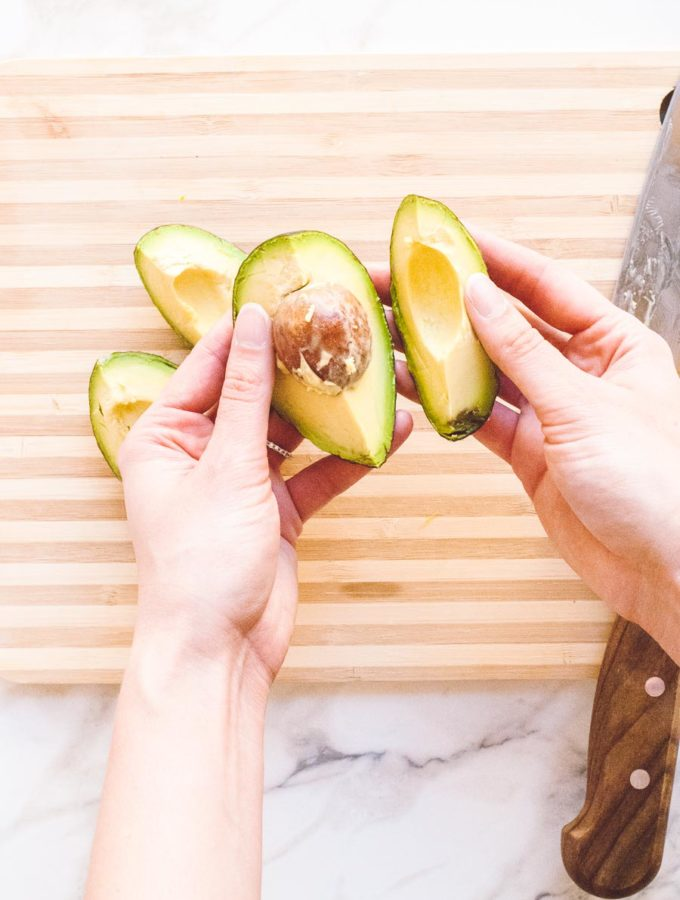 hands demonstrating how to safely remove a pit from an avocado