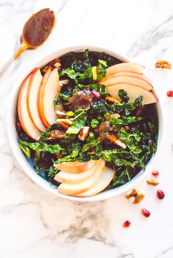Overhead photo of a kale salad with an apple butter vinaigrette, apple butter, and apple slices all tossed into the kale salad.