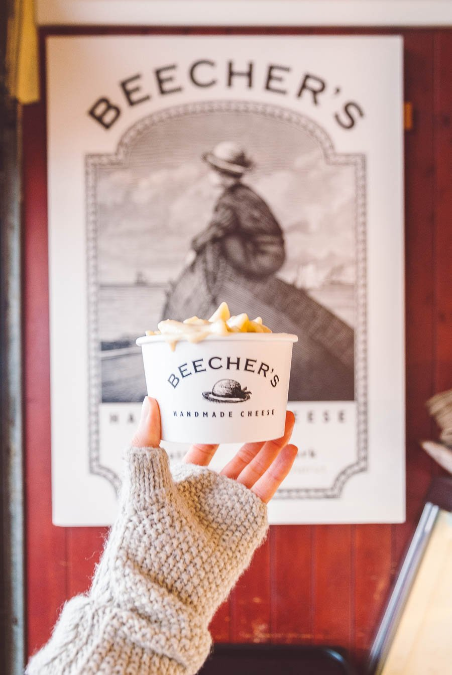Hand holding a cup of Beecher's Mac and Cheese in front of the Beecher's logo in Seattle