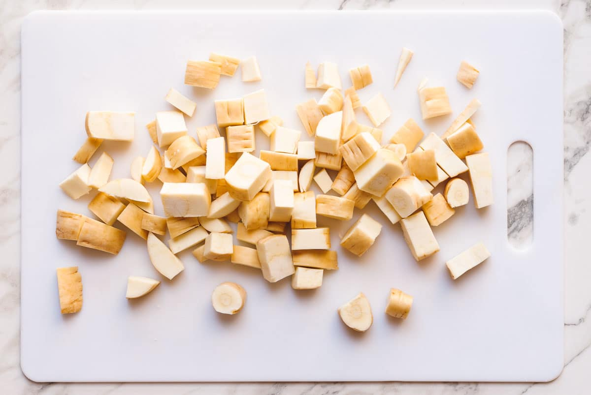 White cutting board with chopped parsnip pieces scattered around.