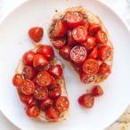 Overhead square image of cherry tomatoes on top of a slice of bread.