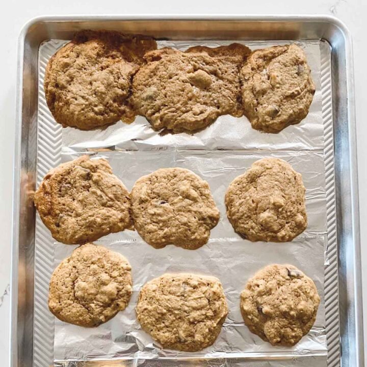 Overhead view of a sheet pan with nine baked cookies with three of the cookies looking runny or watery compared to the others.