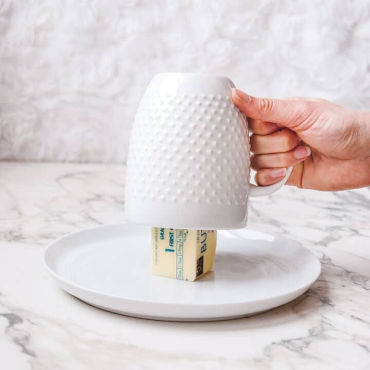 Hand lifting up a white mug that has been inverted and placed over a vertical stick of butter on a white plate.